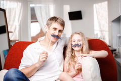 Joyful father and daughter with artificial mustache while sitting togheter on red chair at home. Joyful father and daughter with artificial mustache while Stock Image