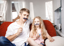 Joyful father and daughter with artificial mustache while sitting togheter on red chair at home. Joyful father and daughter with artificial mustache while Royalty Free Stock Image