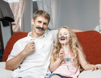 Joyful father and daughter with artificial mustache while sitting togheter on red chair at home. Joyful father and daughter with artificial mustache while Royalty Free Stock Photo