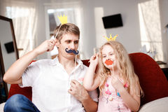 Joyful father and daughter with paper crowns and mustaches while sitting togheter on red chair at home. Joyful father and daughter with paper crowns and Royalty Free Stock Images