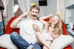 Joyful father and daughter with paper crowns and mustaches while sitting togheter on red chair at home. Joyful father and daughter with paper crowns and Stock Image