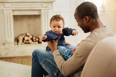 Joyful father entertaining his son. Precious time. Alert loving caring father smiling and amusing his son while sitting on the couch and a fireplace in the Royalty Free Stock Photography