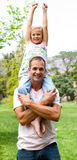 Joyful father giving his daughter piggy-back ride Stock Images