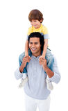 Joyful father giving piggyback ride to his son Stock Images