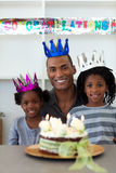 Joyful father with his children celebrating a birt. Joyful Afro-American father with his children celebrating a birthday at home Royalty Free Stock Image