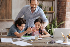 Joyful father and his children washing brushes in a glass Stock Photography