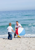 Joyful father and his son playing with a ball. At the beach Royalty Free Stock Photos
