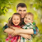 Joyful father hugging his son and daughter. Portrait of joyful father hugging his son and daughter. Fathers day, family holiday, vacation Stock Images