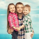 Joyful father hugging his son and daughter. Portrait of joyful father hugging his son and daughter. Fathers day, family holiday, vacation Royalty Free Stock Images
