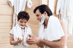 Joyful father inserts shaving foam onto hands of young son. stock photo
