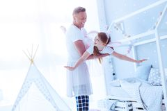 Joyful father lifting daughter while playing with her stock images