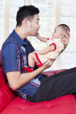 Joyful father play with his kid on sofa Royalty Free Stock Photos