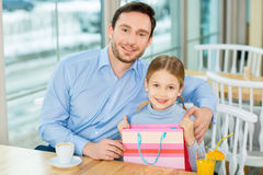 Joyful father sitting and hugging dear kid at the cafeteria. Royalty Free Stock Image