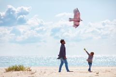 Joyful father and son, family launching the kite on sandy beach, at windy day. Joyful father and son, family launching the bird kite on sandy beach, at windy day stock photography