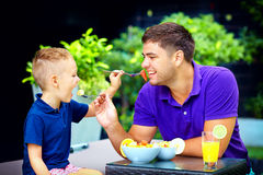 Joyful father and son feeding each other with tasty fruit salad Royalty Free Stock Photo