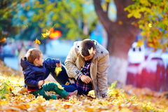Joyful father and son having fun in autumn park Stock Photo