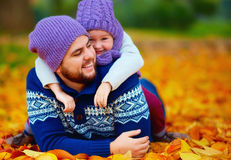 Joyful father and son having fun in autumn park Stock Image