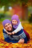 Joyful father and son having fun in autumn park Royalty Free Stock Image