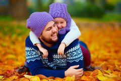 Joyful father and son having fun in autumn park Royalty Free Stock Photos