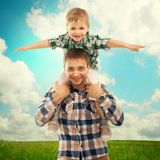 Joyful father with son on shoulders. Carefree and happy. Fathers day, family holiday, vacation Royalty Free Stock Images
