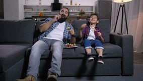 Joyful father and son viewing comedy show on tv. Joyful laughing single dad and cheerful son with tasty fruit kebabs viewing comedy show on tv broadcasting stock video footage