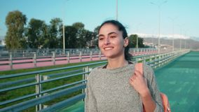 Happy young sportswoman is walking over track of open stadium and smiling. Joyful female athlete is going over road of stadium in sunny day, frontal view of face stock footage