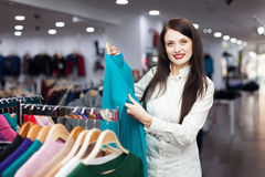 Joyful female buyer choosing sweater Royalty Free Stock Images