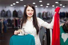 Joyful female buyer with sweaters. Joyful female buyer with two sweaters at clothing store Royalty Free Stock Image