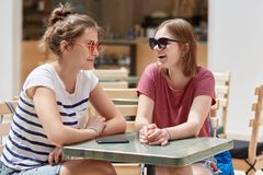 Joyful female companions in shades, have friendly talk in coffee shop while wait for order, have fun together, recreat during summ. Er time, gossip about other stock photography