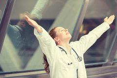 Joyful female doctor standing in hospital hallway with arms raised Royalty Free Stock Images