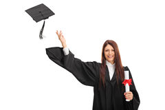 Joyful female graduate throwing her hat Stock Photography