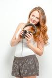 Joyful female holds headphones around neck Stock Photo