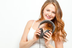 Joyful female holds headphones around neck Stock Photos