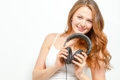 Joyful female holds headphones around neck Stock Photos