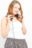 Joyful female holds headphones around neck Royalty Free Stock Images