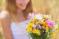Joyful female kid adores field bouquet Stock Photo