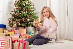 Joyful female kid holding New Year present stock photo