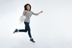 Joyful female person expressing positivity. Jump in the air. Positive woman keeping smile on her face and stretching right leg while hurrying up for classes Stock Photography