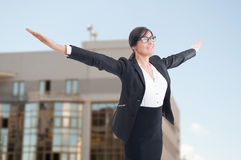 Joyful female realtor with arms outstretched. Celebrating victory or success at her job Royalty Free Stock Photography