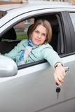 Joyful female sitting in car with ignition key Stock Images