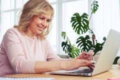 Joyful female smiling while working in laptop Royalty Free Stock Photos