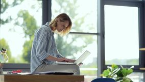 Joyful female student sitting on table while studying online