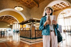 Traveler holding the guidebook. Joyful female traveler holding the guidebook from the information center and looking at the classic hall of train station. young stock photos