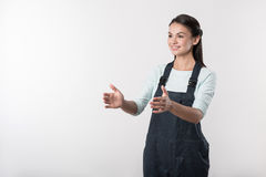 Joyful female worker standing against white background. Involved in work. Pleasant diligent young woman in overalls holding her hands in front of her body and Royalty Free Stock Image