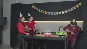 Happy women throwing serpentine on birthday party. Joyful females in cone party hats having fun throwing at each other serpentine celebrating birthday in stock video footage