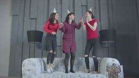 Joyful females in party hats jumping on couch. Excited brunette women having fun during home birthday party jumping on sofa holding hands. Happy family in cone stock video