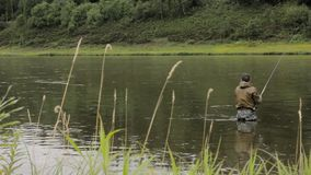 Joyful fisherman is fishing in calm river water near the shore stock video