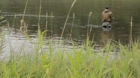 Joyful fisherman is fishing in calm river water near the shore stock footage