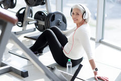 Joyful fit senior woman relaxing with music after workout. Delightful rest. Joyful fit senior woman enjoying rest and listening to music in headphones after Stock Image