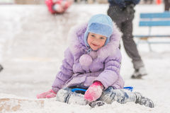 Joyful five years girl has slipped from the icy hill Royalty Free Stock Images